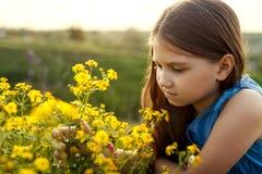 Маленькая девочка пахнуть желтым цветком Стоковая Фотография RF