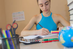 Маленькая девочка пишет в тетради между книгами Концепция образования - книги на столе Стоковое Изображение RF