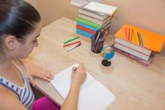 Маленькая девочка пишет в тетради между книгами Концепция образования - книги на столе Стоковая Фотография