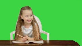 Маленькая девочка пишет к сочинительств-книге на зеленом экране, ключу chroma сток-видео