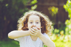 Маленькая девочка покрывая ее рот Стоковая Фотография