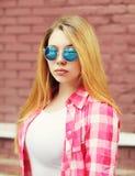 Маленькая девочка портрета нося checkered рубашку и солнечные очки стоковое изображение
