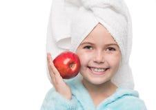 маленькая девочка после принимать ливень держа красное яблоко около ее c Стоковое фото RF