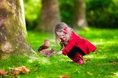 Маленькая девочка подавая белка в парке осени Стоковое Фото