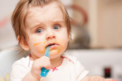 Маленькая девочка подавая от ложки на голубом стуле Стоковое фото RF