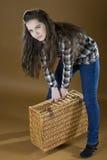 Маленькая девочка поднимает тяжелую сплетенную сумку Стоковое Изображение