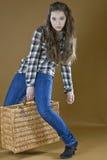 Маленькая девочка поднимает тяжелую сплетенную сумку Стоковые Изображения