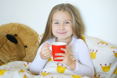 Маленькая девочка получить и выпивая горячий чай с лимоном в кровати Стоковая Фотография