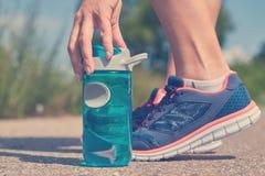 Маленькая девочка принимает бутылку спорт воды к питью, ногам в тапках стоковое изображение rf