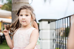 Маленькая девочка при голубые глазы касаясь ее волосам Стоковое Изображение