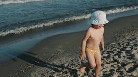 Маленькая девочка при ее мать играя на пляже акции видеоматериалы