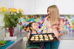 Маленькая девочка при ее мать подготавливая печенье на кухне стоковое фото