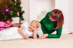 Маленькая девочка при ее мать сидя на рождестве Стоковое Изображение