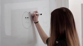 Маленькая девочка при длинные волосы рисуя счастливую сторону smiley с отметкой на белой доске сток-видео
