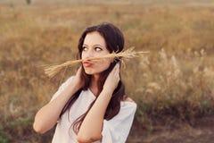 Маленькая девочка при длинные коричневые волосы делая усик с колоском стоковое фото rf