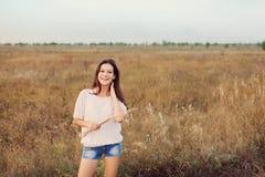 Маленькая девочка при длинные коричневые волосы стоя на луге осени стоковая фотография