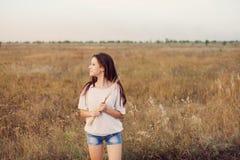 Маленькая девочка при длинные коричневые волосы стоя на луге осени стоковые фотографии rf