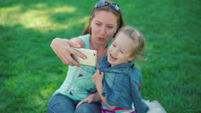 Маленькая девочка при мать отдыхая в парке, делает selfie сток-видео