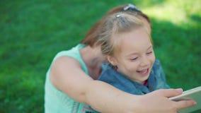 Маленькая девочка при мать отдыхая в парке, делает selfie акции видеоматериалы