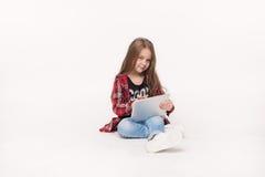 Маленькая девочка при ПК таблетки изолированный на белой предпосылке Стоковое Изображение RF