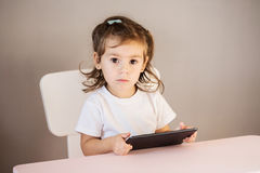 Маленькая девочка при ПК таблетки сидя на таблице Стоковое фото RF