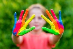 Маленькая девочка при руки покрашенные в красочных красках готовых для руки печатает Стоковые Изображения RF