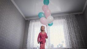 Маленькая девочка при светлые волосы, одетые в розовой блузке и брюках скача на кровать, которая стоит перед окном акции видеоматериалы