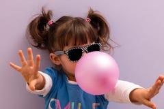Маленькая девочка при стекла солнца дуя - вверх по розовой жевательной резине Стоковое Изображение
