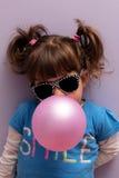 Маленькая девочка при стекла солнца дуя - вверх по розовой жевательной резине Стоковое фото RF