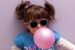Маленькая девочка при стекла солнца дуя - вверх по розовой жевательной резине Стоковая Фотография RF