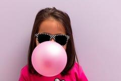 Маленькая девочка при стекла солнца дуя - вверх по розовой жевательной резине Стоковое Изображение RF