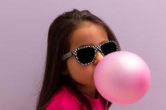 Маленькая девочка при стекла солнца дуя - вверх по розовой жевательной резине Стоковая Фотография