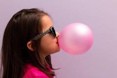 Маленькая девочка при стекла солнца дуя - вверх по розовой жевательной резине Стоковые Фото