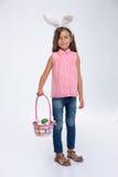 Маленькая девочка при уши кролика держа корзину яичек Стоковое фото RF