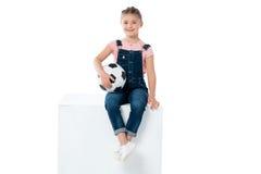 Маленькая девочка при футбольный мяч сидя на кубе изолированном на белизне Стоковые Изображения RF