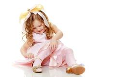 Маленькая девочка пробуя на ботинках стоковое изображение