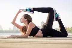 Маленькая девочка протягивает на представлении йоги во время outdoo разминки тренировки Стоковые Фото
