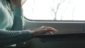 Маленькая девочка путешествуя в поезде и используя тетрадь Женские руки используя сенсорную панель ПК компьтер-книжки Девушка бес видеоматериал