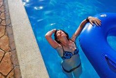 Маленькая девочка плавает в бассейне с резиновым кольцом Она бросала назад голову и полощет волосы Стоковая Фотография