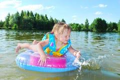 Маленькая девочка плавает в реке. Стоковое Изображение