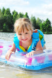 Маленькая девочка плавает в реке. Стоковое Изображение RF