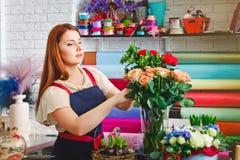 Маленькая девочка работая в цветочном магазине, женщина флориста делает букет Стоковая Фотография RF
