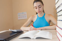 Маленькая девочка работая на его домашней работе Концепция образования - книги на столе Стоковые Фотографии RF