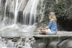 Маленькая девочка размышляя на водопаде Стоковые Изображения RF