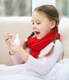 Маленькая девочка распыляя ее нос стоковая фотография rf