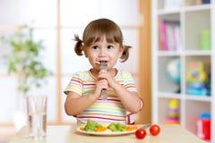 Маленькая девочка рассматривает ростки Брюсселя Ребенок при здоровая еда сидя на таблице в питомнике Стоковая Фотография RF