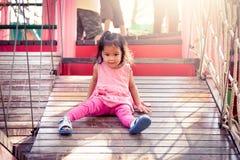 Маленькая девочка ребенка играя на скольжениях детей на спортивной площадке Стоковое фото RF