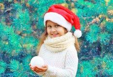 Маленькая девочка ребенка портрета рождества усмехаясь в снежном коме удерживания шляпы santa красном около дерева ветви Стоковое Изображение RF