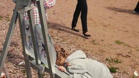 Маленькая девочка рисует изображение на мольберте в парке на фестивале лета Концентрация акции видеоматериалы
