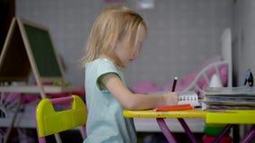 Маленькая девочка рисует изображение с карандашами в студии сидя на таблице Малый ребенок учит покрасить с акции видеоматериалы